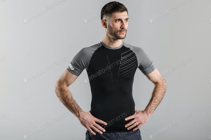 Bild des jungen unrasierten Mannes in Sportbekleidung posieren und beiseite schauen