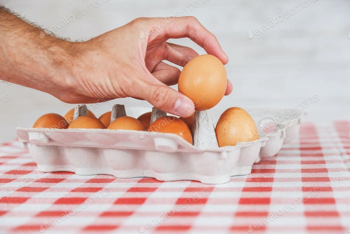Man taking egg from cardboard container