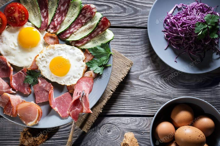 Fried eggs with vegetables and bacon on a wooden table