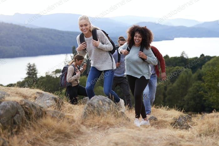 A group of five young adult friends smiling while hiking together to a mountain summit