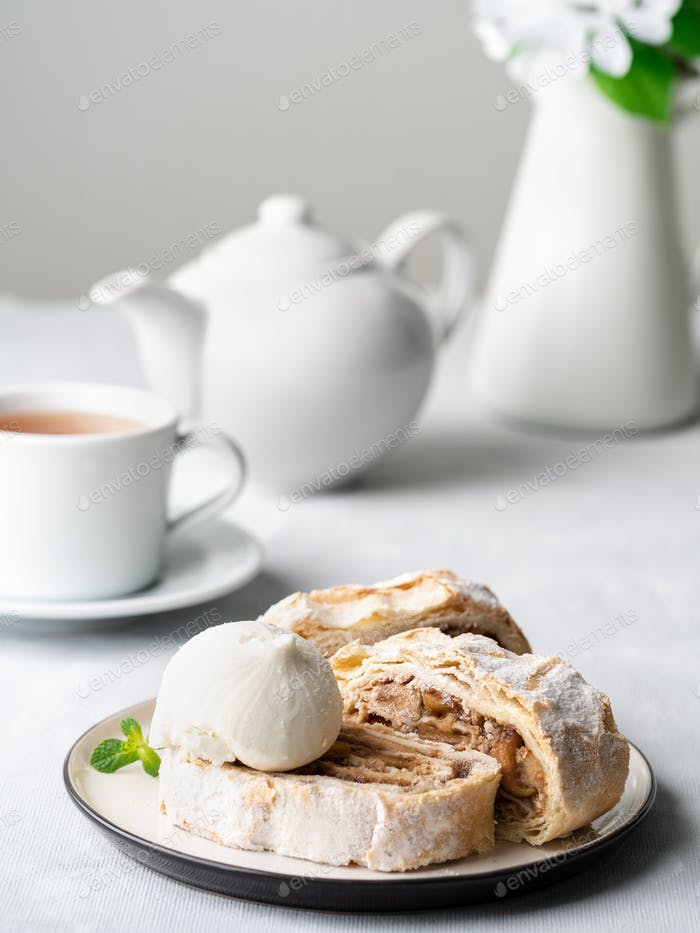 Apple strudel with ice cream and cinnamon. Baked cake and tea, delicious dessert