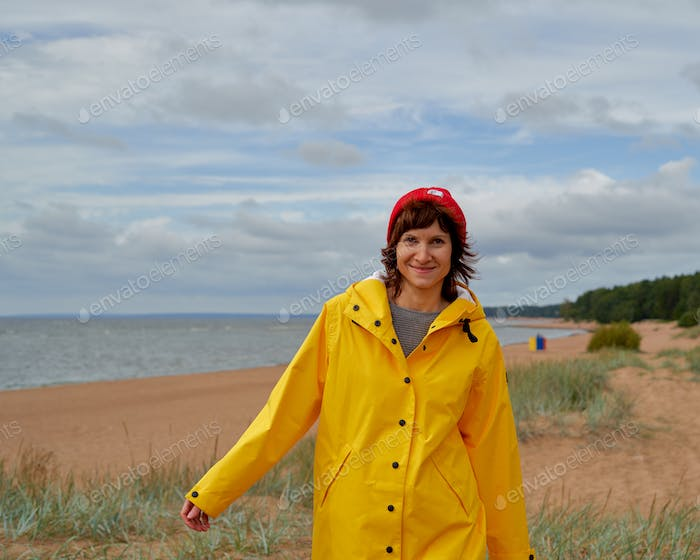 Waist portrait of mature woman in yellow raincoat and red hat walking along beach