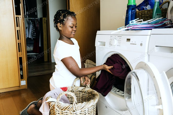 Young teen girl washing clothes using washing machine