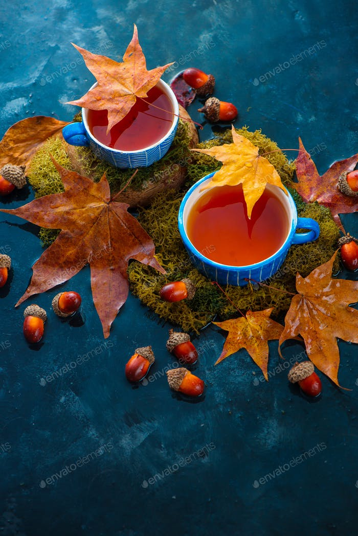 Autumn tea with a blue handmade ceramic cup, acorns and fallen maple leaves. Seasonal drink