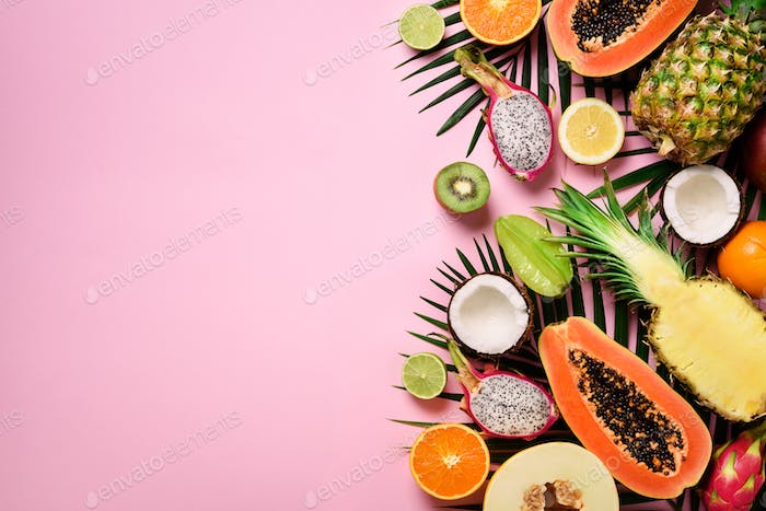 Exotic fruits and tropical palm leaves on pastel pink background - papaya, mango, pineapple, banana