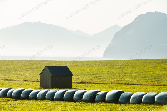 Rural scene with farm field and hay stacks