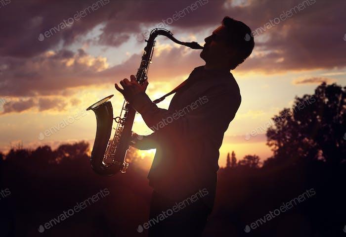 Saxophonist spielt Saxophon gegen Sonnenuntergang