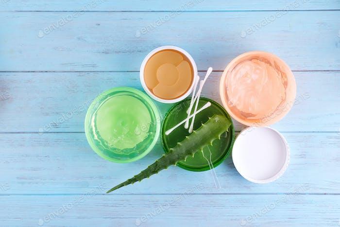 gel of snail, eye patch and Fresh Aloe Vera Gel in jar on blue wooden background. Snail gel is