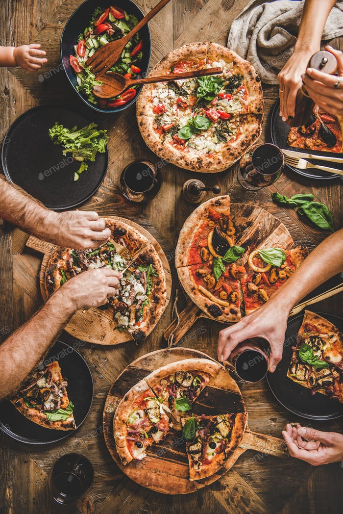Family having pizza dinner party with red wine, top view