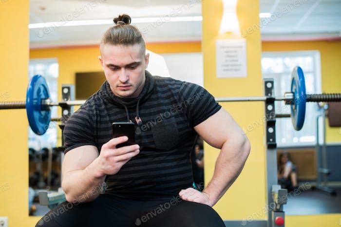 Junge gutaussehende Mann mit Telefon während der Übung Pause im Fitnessstudio.