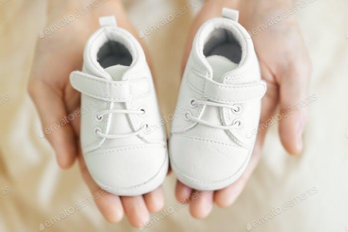 Kleine niedliche Babyschuhe in Vaterhänden