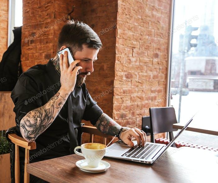 El tipo con tattos llamando por teléfono