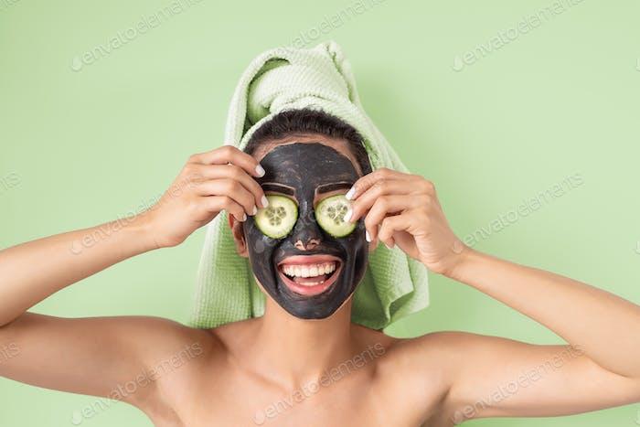 Happy smiling girl applying facial carbon mask portrait