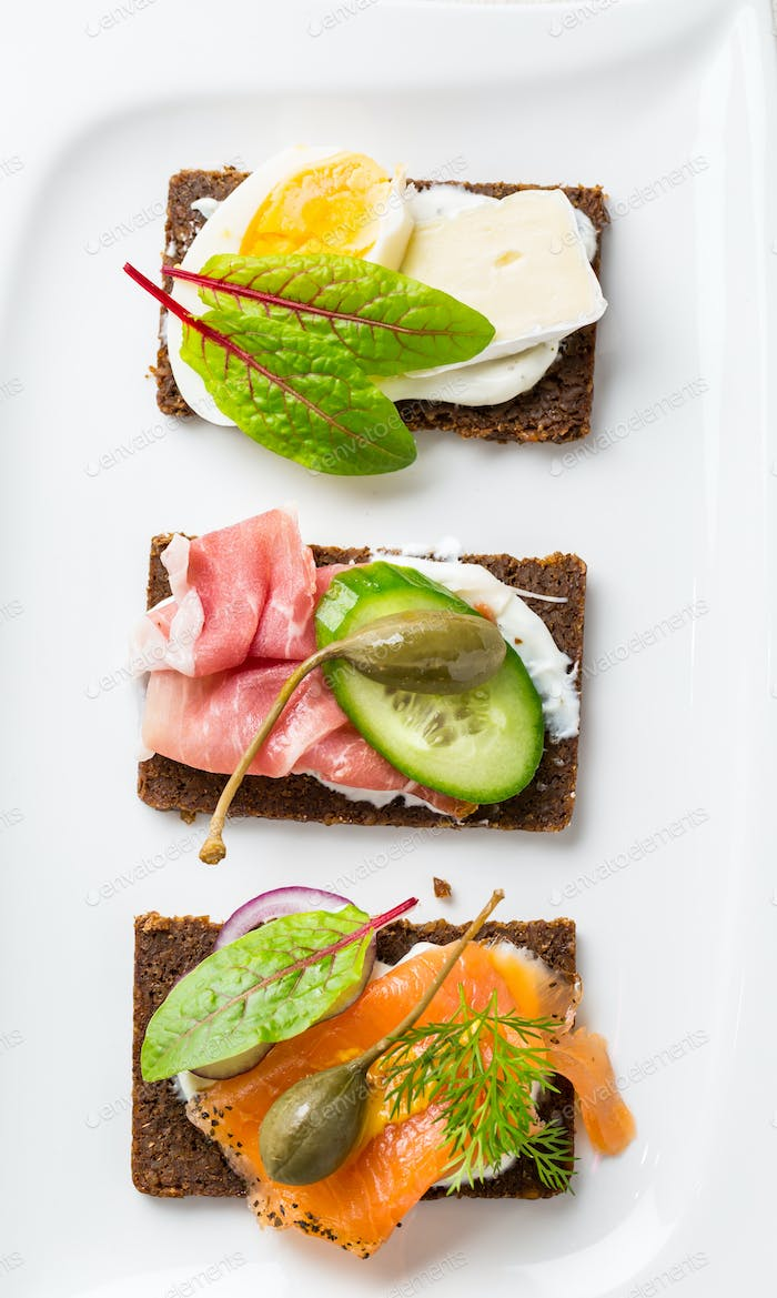Variation of healthy open sandwiches on Pumpernickel bread with vegetables, salmon, ham
