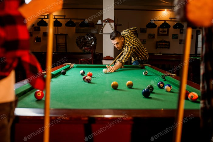 Friends plays american billiard in poolroom