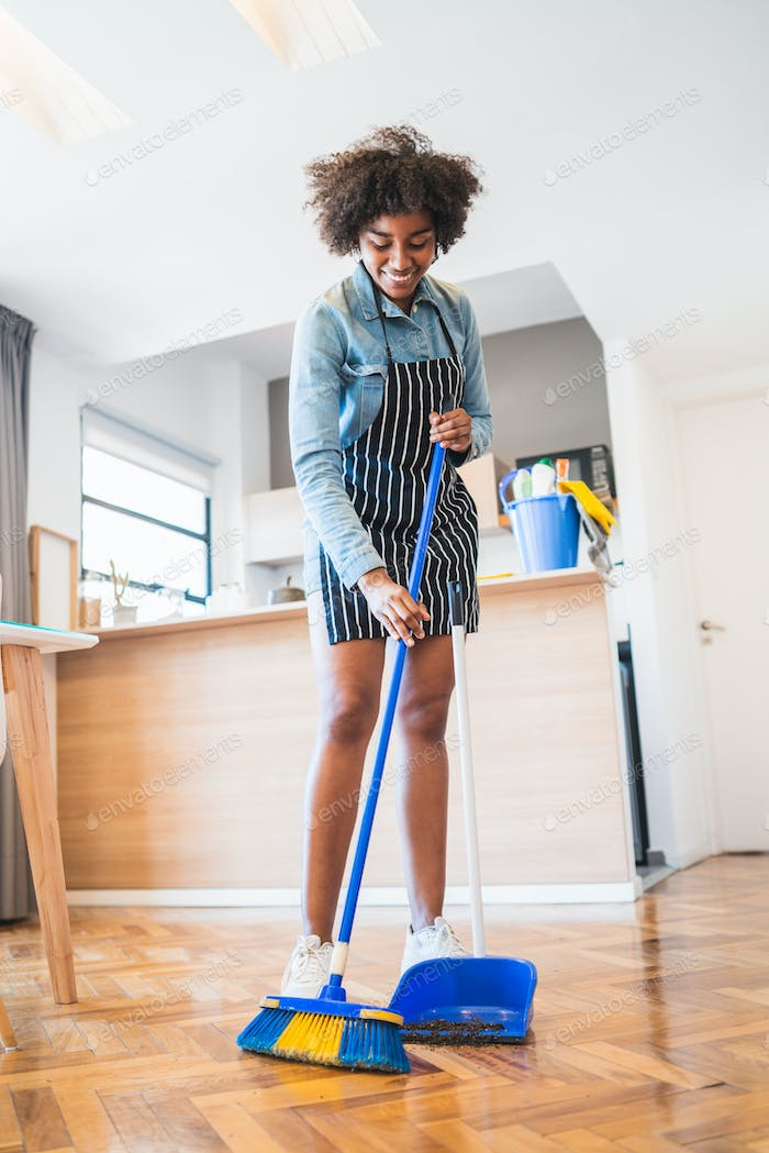 Afro woman sweeping floor with broom at home.