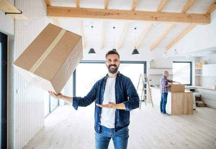 A mature man holding a large box in one hand when furnishing new house.