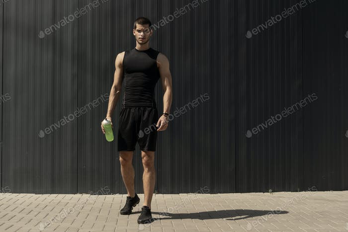 Athletic modern young man posing on a gray metallic wall copy sp