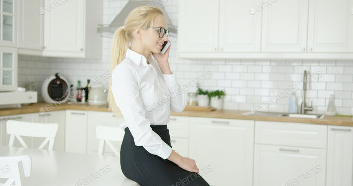 Confident young woman talking by phone