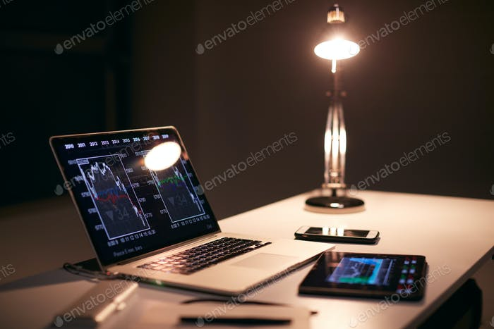 Desk Of  Share Trader At Desk With Stock Price Data Displayed On Laptop And Digital Tablet