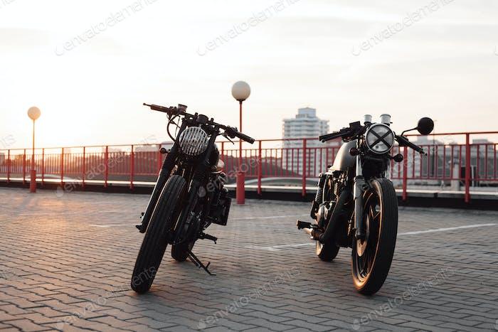 Zwei Oldtimer-Motorrad auf Parkplatz während Sonnenuntergang