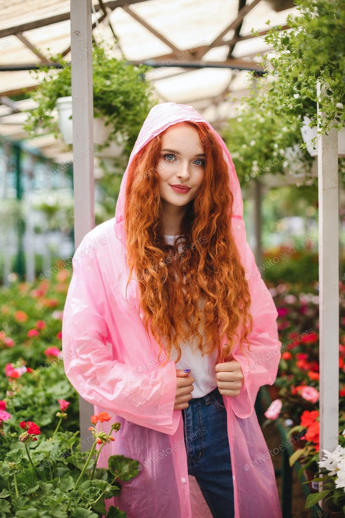 Beautiful lady with redhead curly hair standing in pink raincoat and dreamily looking in camera