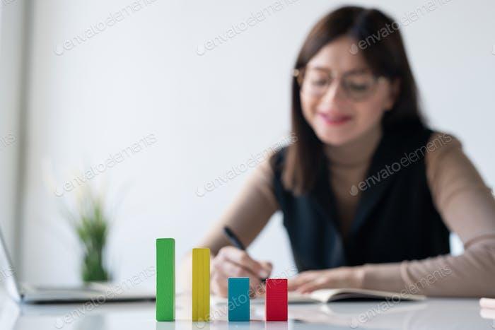 Multi-color cube chart on desk on background of female banker making notes