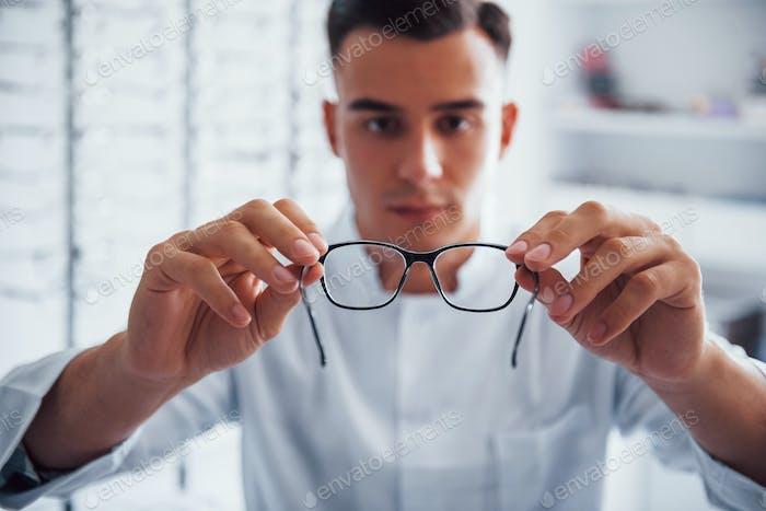 Fokussiertes Foto von brandneuen Brillen, die der junge Augenarzt drinnen hält