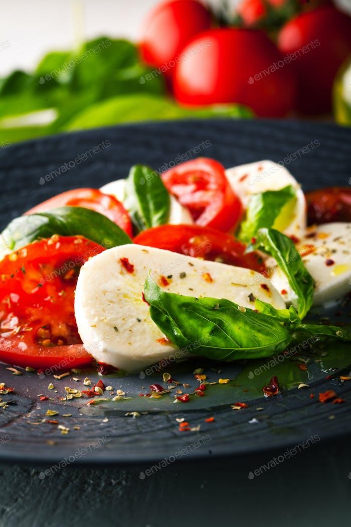 Caprese salad with mozzarella, fresh tomato and basil