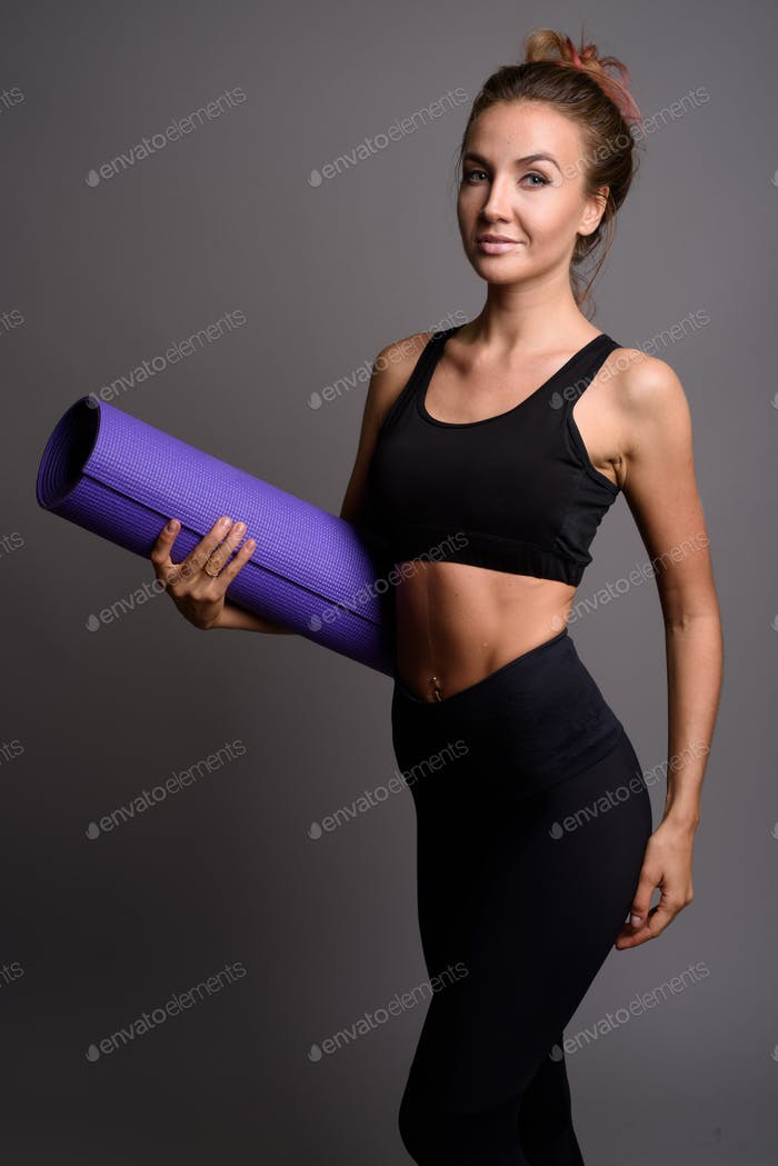 Young beautiful woman ready for gym against gray background