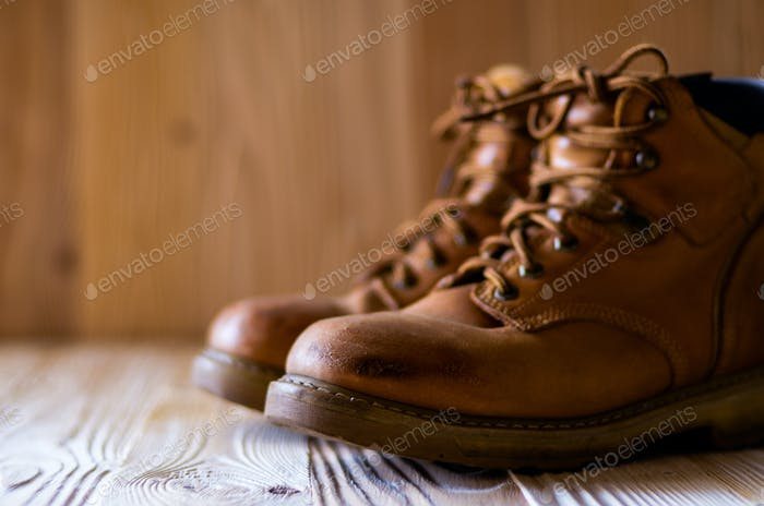 Yellow leather used work boots on wooden background closeup. Pla