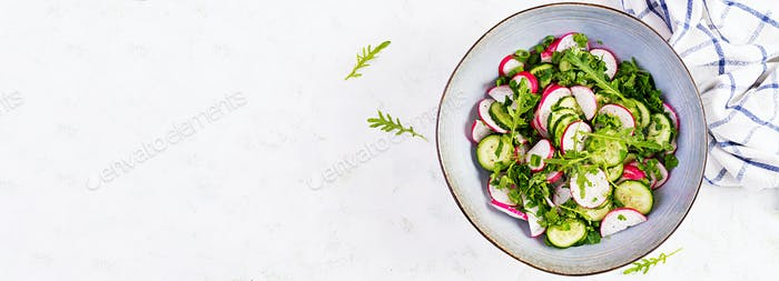 Vegetarian vegetable salad of radish, cucumbers, arugula and green onions.