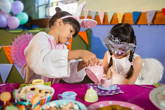 Kids playing with tea set during birthday party