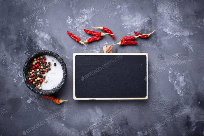 Mix of peppers and salt on gray background