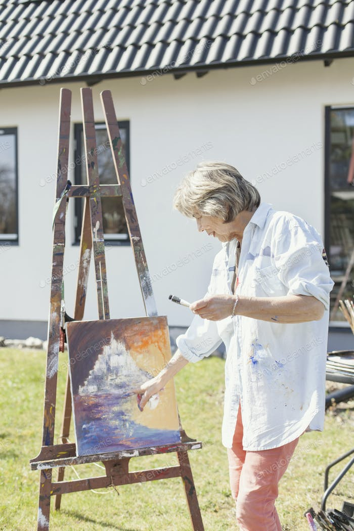 Senior female artist painting at easel in backyard
