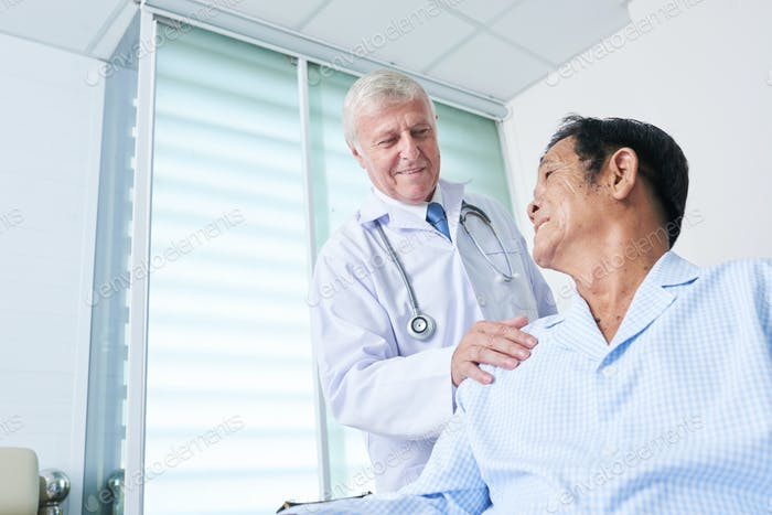 General practitioner patting shoulder of senior patient