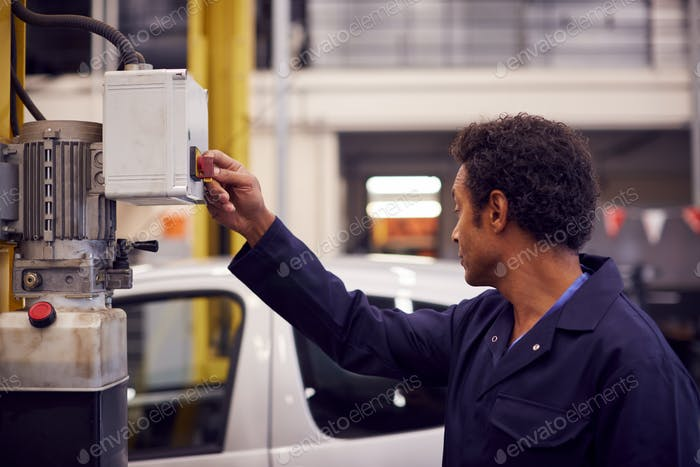 Male Motor Mechanic Raising Car On Hydraulic Lift In Garage
