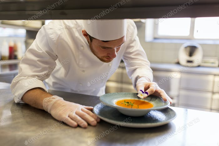 male chef decorating dish with pansy flower