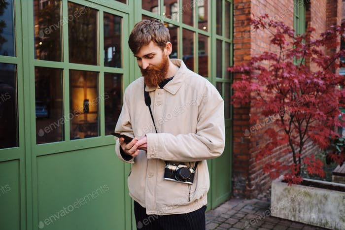 Young bearded man with camera intently using cellphone outdoor