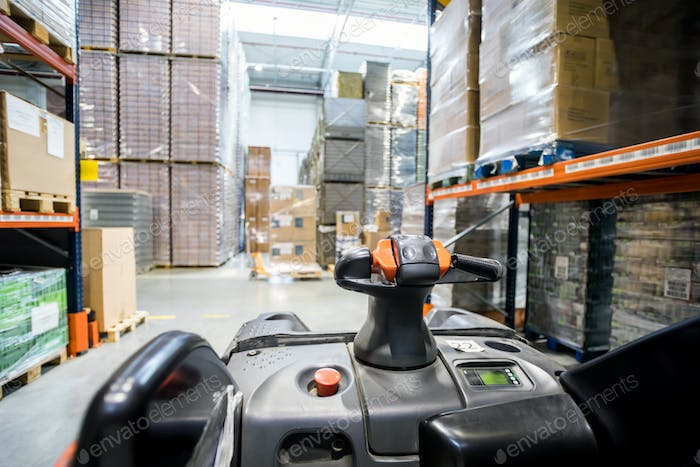 Forklift steering wheel in warehouse among packages