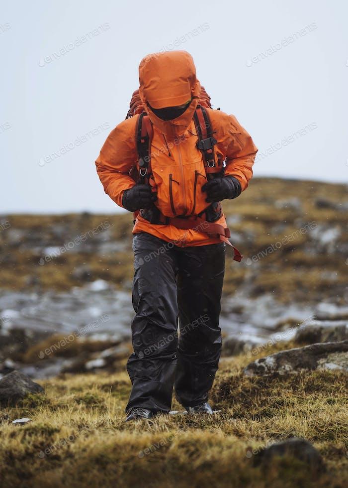 Woman in an orange windbreaker hiking under the rain at the Faroe Islands