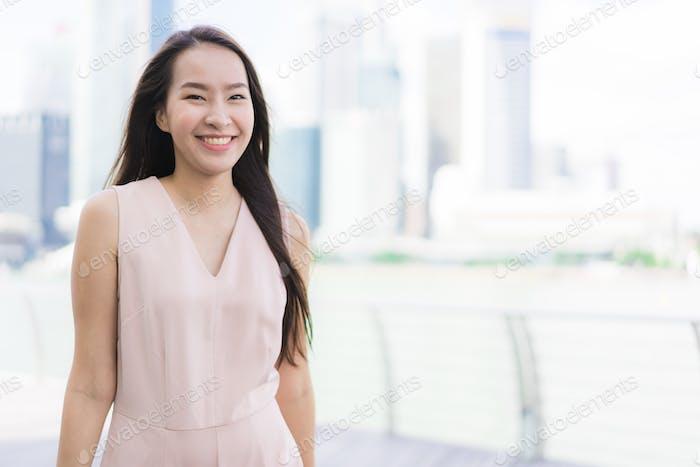 Schöne asiatische Frau lächeln und glücklich, in Singapur zit reisen