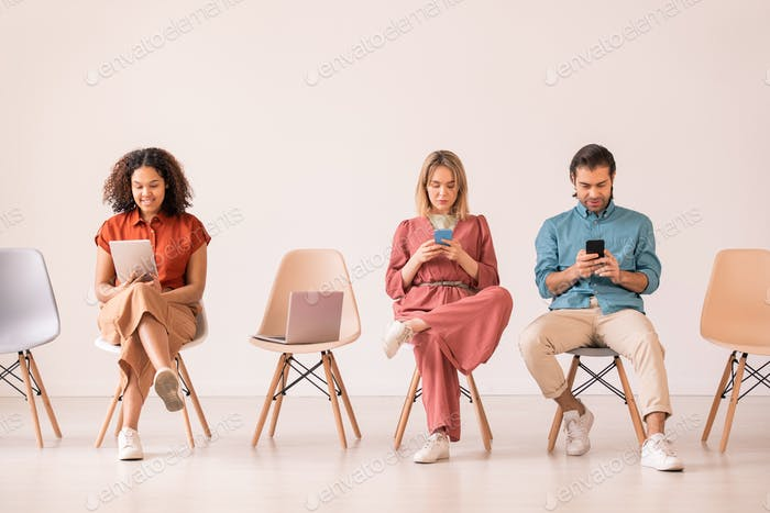 Group of intercultural millennials in casualwear scrolling in their gadgets
