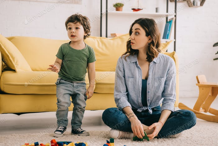 Mother and son playing with toy blocks on carpet