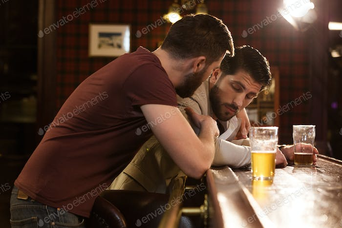 Young man talking to his drunk friend