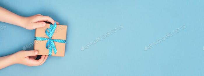 Kinderhände in Geschenkbox. Blaues Banner.