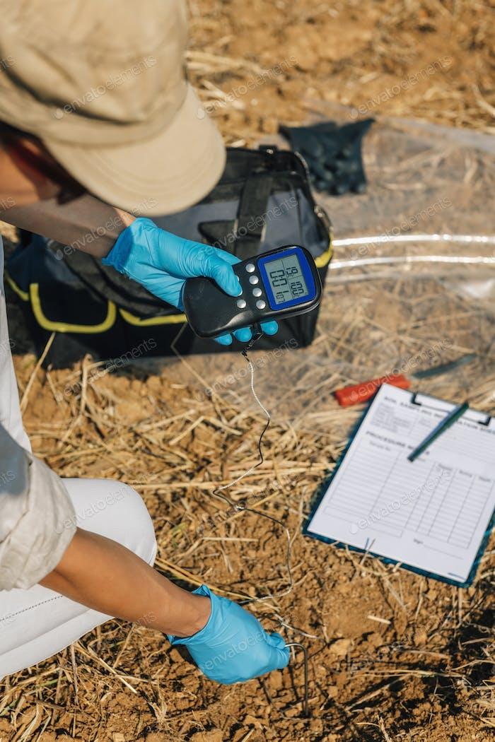 Soil Thermometer. Female Agronomist Measuring Soil Temperature