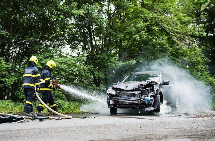Zwei Feuerwehrleute löschen nach einem Unfall ein brennendes Auto.