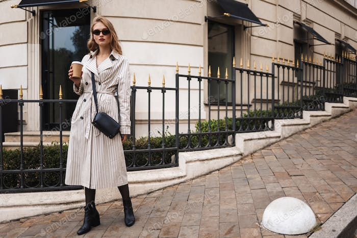 Young attractive woman in striped trench coat and sunglasses wit