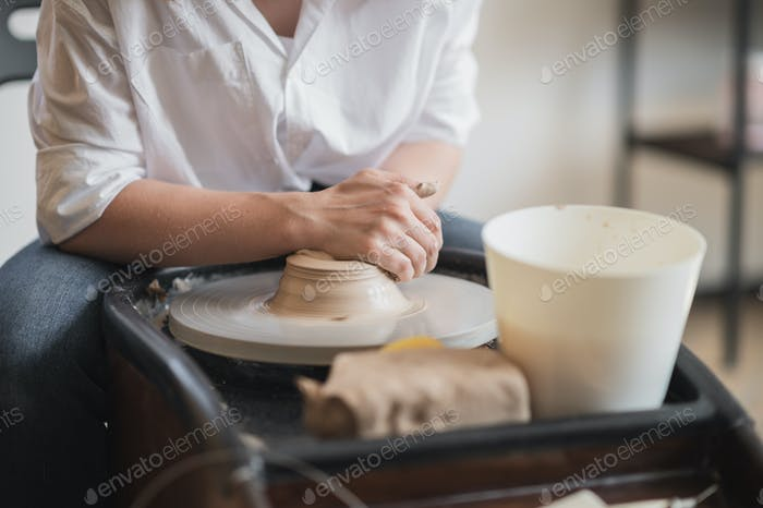The manufacture of ceramics. Woman prepare clay for work on pottery wheel. Close up view of hands